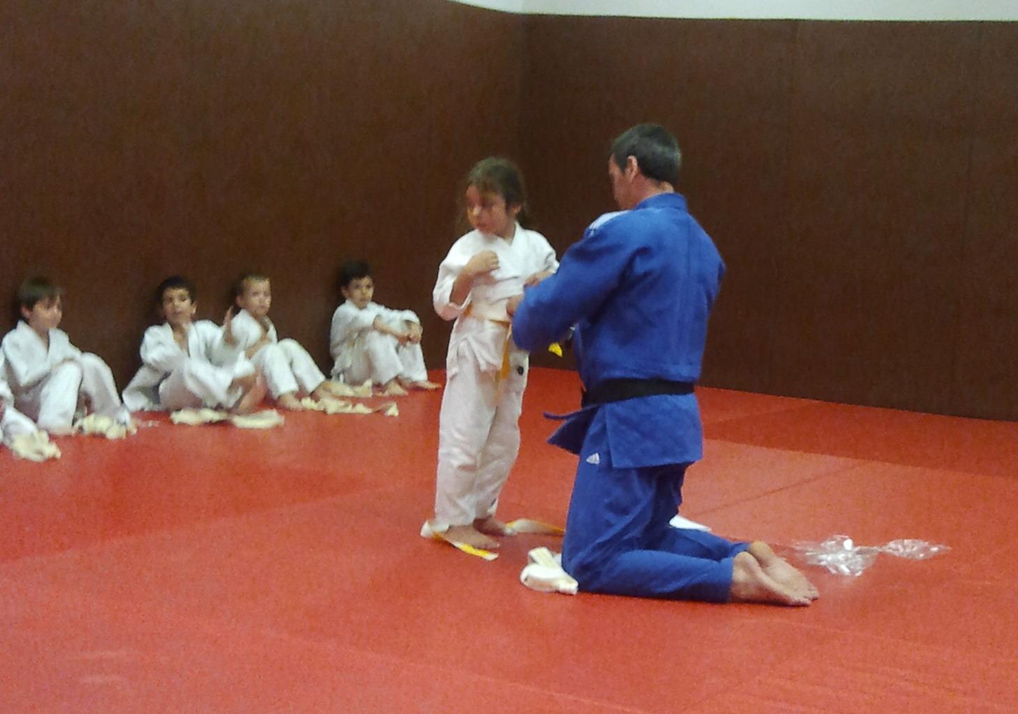 Passage de la ceinture blanche à la ceinture blanche jaune. Le maître remet  à chaque enfant sa nouvelle ceinture 4b6efd423b5